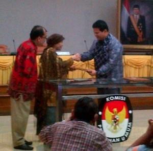 Husni Kamil Manik (Ketua KPU) berjabat tangan dengan Ariani Sukanwo (Ketua PPUA Penca), didampingi Heppy Sebayang (Program Manager AGENDA)